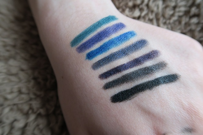 The swatches of the Urban Decay 24/7 Glide On Eye Pencils on Lucy's hand