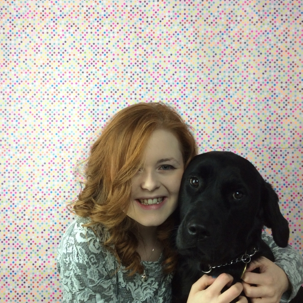Lucy and her guide dog Olga hugging on a dotty background